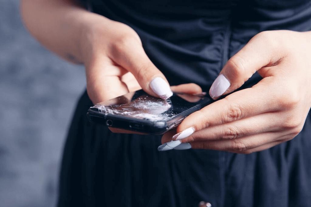 kobieta trzyma telefon z pękniętą szybką lub wyświetlaczem